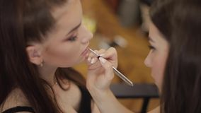 Makeup artist applies lipstick. Hand of make-up master, painting lips of young beauty redhead model. Make up in process stock video