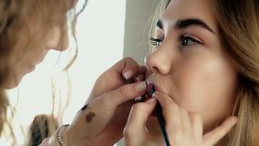 Makeup artist applies makeup. Model is young beauty girl, making lips close-up stock video footage