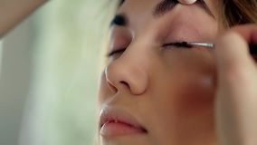 Makeup artist applies makeup. Model is young girl, Master Class, making eyes stock footage