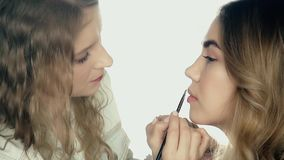 Makeup artist applies makeup. Model is young beauty girl, making lips, close up stock footage