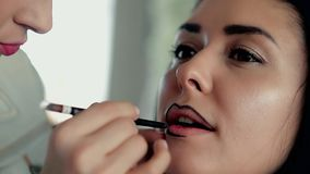 Makeup artist applies makeup. Model is young girl, Master Class, making outlines of lips, close up stock footage