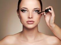Makeup artist applies mascara. Beautiful woman face. beauty girl with make-up Stock Image