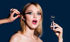 Makeup artist applies mascara to the eyelashes. Bright red lips makeup, perfect clean skin, eye shadows. Woman doing her. Make up using black mascara brushing stock photography