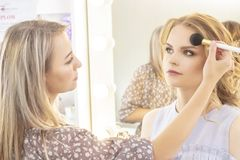 Makeup artist applies model makeup on face. bridal makeup, light evening make-up in nude tones stock photos