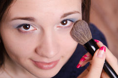 Makeup artist applies powder on face of beautiful girl Stock Photos