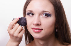 Makeup artist applies powder on face of beautiful model Stock Photos