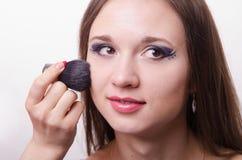 Makeup artist applies powder on face of beautiful model Stock Photos