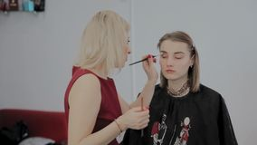 Makeup artist applies professional makeup to a beautiful young girl. New concept in makeup. Makeup artist applies professional makeup to a beautiful young girl stock footage