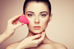 Makeup artist applies skintone Stock Images