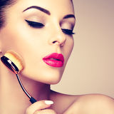 Makeup artist applies skintone with brush Royalty Free Stock Photography
