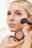 Makeup artist apply blush on cheeks. With blush brush stock image