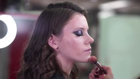 Makeup artist apply makeup to an attractive young model for photo session stock footage