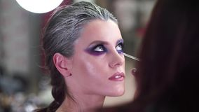 Makeup artist apply makeup to an attractive young model for photo session. Eyes. stock video footage