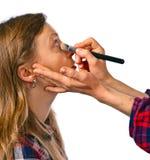 Makeup artist apply makeup to a model Royalty Free Stock Image
