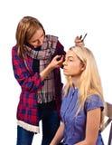 Makeup artist apply makeup to a model Royalty Free Stock Photos