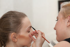 Makeup artist apply makeup young girl before the photoshoot Royalty Free Stock Image