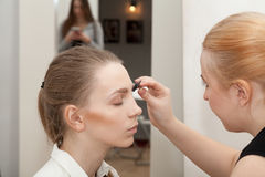 Makeup artist apply makeup young girl before the photoshoot Stock Images