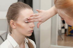 Makeup artist apply makeup young girl before the photoshoot Royalty Free Stock Photography