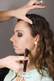 Makeup artist applying base foundation to model Stock Image