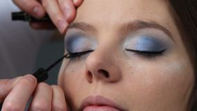 Makeup artist applying black eye liner to model eye. Full HD. Cosmetic beauty procedures and makeover concept. Closeup woman face eyes painting. Makeup artist stock video