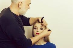 Makeup artist applying black mascara on girl eyelashes Stock Image