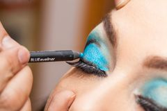 Applying blue eyeshadow on white woman eyes Royalty Free Stock Image