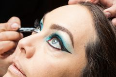 Applying blue eyeshadow on white woman eyes Stock Image
