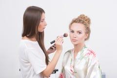 Makeup artist on applying blush on cheeks with Stock Image