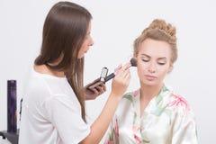 Makeup artist on applying blush on cheeks with Stock Photos
