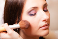 Makeup artist applying with brush powder rouge on female check Royalty Free Stock Image