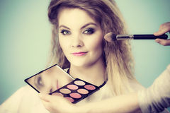 Makeup artist applying with brush rouge on female check Royalty Free Stock Images