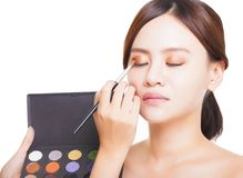 Makeup artist applying colorful eyeshadow on model's eye with a Royalty Free Stock Images