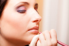 Makeup artist applying cosmetic on lips woman Royalty Free Stock Photo