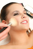 Makeup artist applying cosmetics. Cosmetician applying makeup to the model with a brush Stock Photography