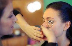 Makeup artist applying eyelash curler Stock Photography