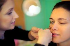 Makeup artist applying eyelash curler Royalty Free Stock Image