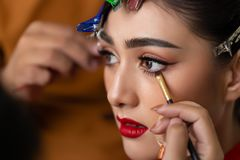 Makeup artist applying eyeliner to waterline by using eyeliner brush for making perfect makeup before charming beautiful model do royalty free stock images