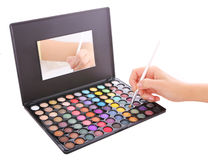 Makeup artist applying eyeshadow on brush Stock Photos