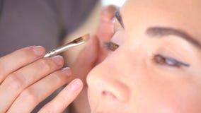 Makeup artist applying eyeshadow on eyelid using makeup brush. Close up stock video footage