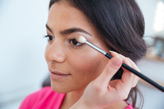 Makeup artist applying eyeshadow to attractive woman Stock Images