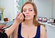 Makeup artist applying eyeshadow on womans eyes Royalty Free Stock Photography