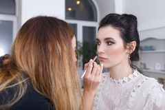 Makeup artist applying lip contour with pencil. Professional makeup artist applying makeup for young woman. Closeup portrait of make up artist at work in her Royalty Free Stock Image