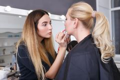 Makeup artist applying lip contour with pencil. Professional makeup artist applying makeup for young woman. Closeup portrait of make up artist at work in her Stock Images