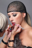 Makeup artist applying lip gloss on face of the woman. Beauty girl with makeup lip gloss and hairnet. Bright holiday make-up for blond woman with brown eyes Royalty Free Stock Photo