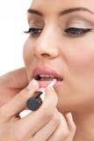 Makeup artist applying  lips-gloss on model Stock Image