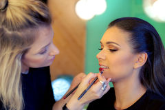Makeup artist applying lipstick. Makeup artist creating beautiful makeup for brunette model Royalty Free Stock Image