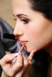Makeup artist applying lipstick on the lips Royalty Free Stock Photo