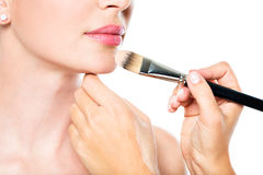 Makeup artist applying liquid tonal foundation  on the face. Of the woman Royalty Free Stock Photo