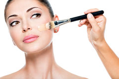 Makeup artist applying liquid tonal foundation  on the face Royalty Free Stock Image