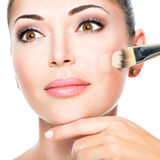 Makeup artist applying liquid tonal foundation  on the face Stock Images